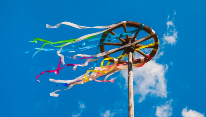 Wooden wheel with colorful ribbons on blue sky background. Slavic celebration of Midsummer